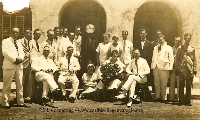 Ambstjubileum J.W.P. Peiliker (1893-1974) bij de Landsradiodienst op 25-08-1934. Peiliker (zittend 2de van links) dochter Zita Peiliker (midden op de grond), echtgenote Julia Peiliker-Jacobs (zittend 4de van links) en Louis C.H.M. Bergman (staand links naast het staand horloge). Foto: Collectie Louis (Manu) Bergman